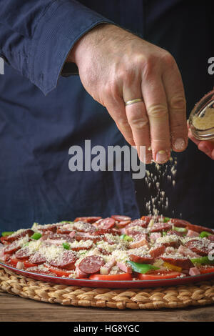 Man in a blue shirt sprinkle with cheese pizza on the table vertical - Stock Photo