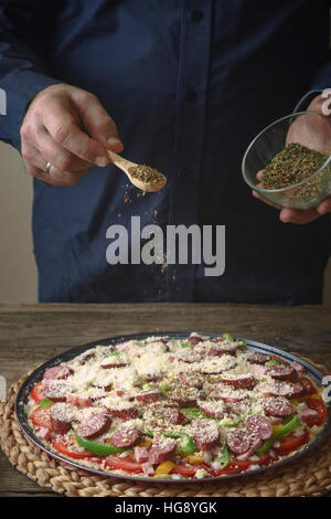 Man in a blue shirt sprinkle with spice pizza from a glass sauser vertical - Stock Photo
