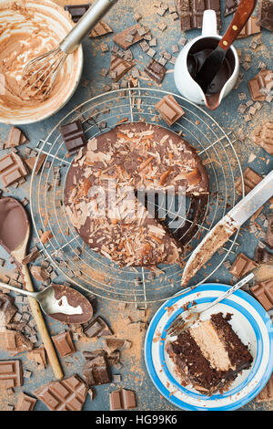 A mess of chocolate. Chocolate cake, bars, chunks and powder pattern on slate - Stock Photo