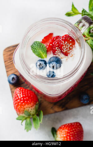 Strawberry smoothie topped with fresh strawberries, blueberries, chia seeds and mint leaf served in glass cup - Stock Photo