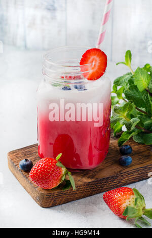 Strawberry smoothie in glass jar with cocktail tube for drinking. Refreshing cold summer drink - Stock Photo