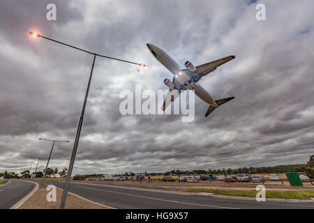 Passenger jet airplane flying low in the sky right above glowing street lights in stormy weather - Stock Photo