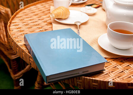 cup of tea croissant book on table - Stock Photo