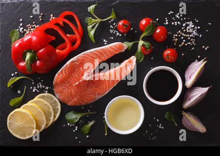 Raw salmon steak and ingredients on a black chopping board. Horizontal top view - Stock Photo