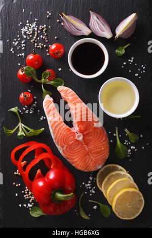 Raw salmon steak and ingredients on a black chopping board. vertical top view - Stock Photo