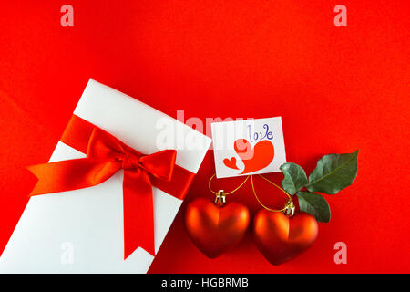 Valentines gift box with a red bow on red background. Image of Valentines day. - Stock Photo