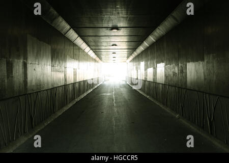Light At The End Of The Tunnel Pedestrian tunnel illuminated by bright sunlight at the exit - Stock Photo