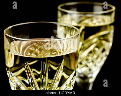 Chilled White Wine in a Cut Crystal Glass Against a Black Background - Stock Photo