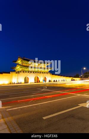 Long exposure car lights leaving trailing streak in front of Gwanghwamun main gate to historic Gyeongbokgung Palace - Stock Photo