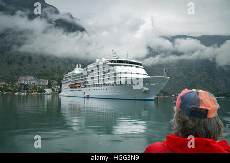 A cruise ship anchors at the Bay of Kotor in misty weather as a sightseer looks on. - Stock Photo