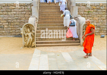 The Buddhist monk in bright orange robe at the staircase to Bodhi Tree Temple, with the guardstone of Naga-Raja - Stock Photo