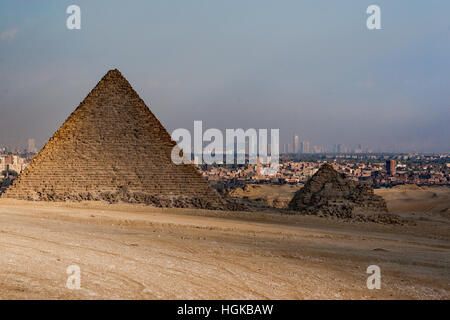 The smallest of the pyramids in Giza is in ruins but its neighbor is still intact and the city of Cairo is in the - Stock Photo