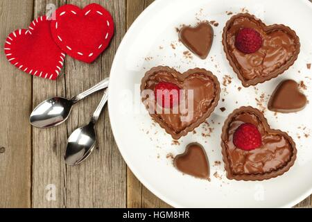 Heart shaped chocolate dessert cups with pudding and raspberries on plate with wood background - Stock Photo
