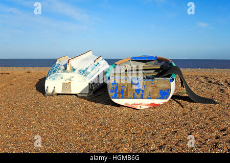 Two small boats, one upright and one overturned, on the beach at Cley next the Sea, Norfolk, England, United Kingdom. - Stock Photo