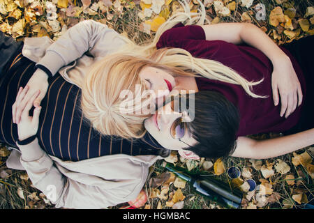 Young couple lying on the floor in a park in autumn - Stock Photo