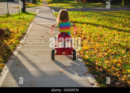 A young girl rides a tricycle in a small town in the United States. - Stock Photo