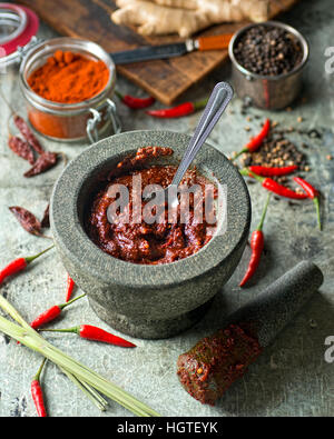 A delicious Thai red curry paste with mortar and pestle. - Stock Photo