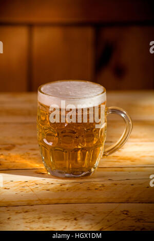 pint of beer on table with afternoon sun light - Stock Photo