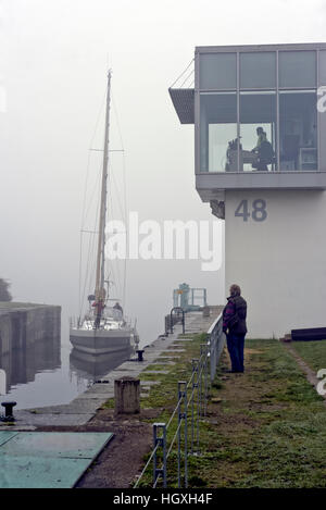 locking operations in thick winter fog at Chatelier Lock Le Lyvet Rance Valley River Rance Brittany France - Stock Photo