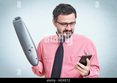 Cheerful young man using a vacuum cleaner looking in his mobile phone - Stock Photo