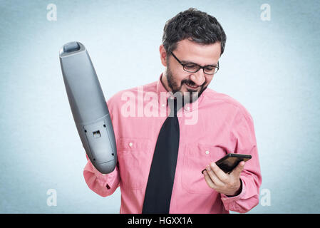 Smiling young man with handheld vacuum cleaner looking at his cell phone - Stock Photo