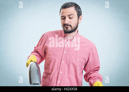 Smiling young man with handheld vacuum cleaner - Stock Photo