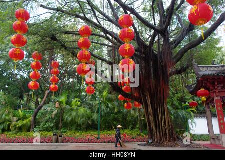 Splendid China Folk:  a beautiful tree, bright red lanterns hanging from its branches, a worker standing sweeping - Stock Photo