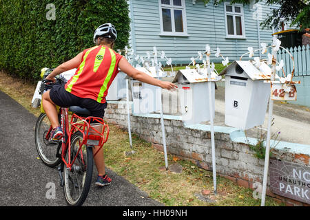 A postal worker in New Zealand delivering letters. - Stock Photo
