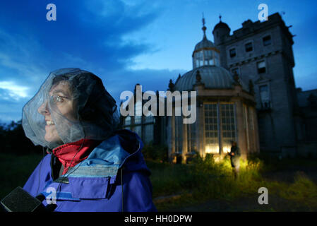 woman, wearing protective net for insects, out bat watching with spooky abandoned house in background - Stock Photo