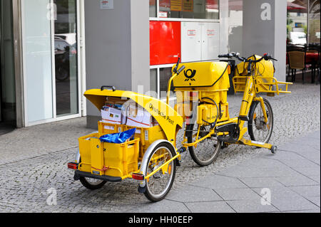 A yellow bicycle mail delivery parked outside an office in Berlin, Germany. - Stock Photo