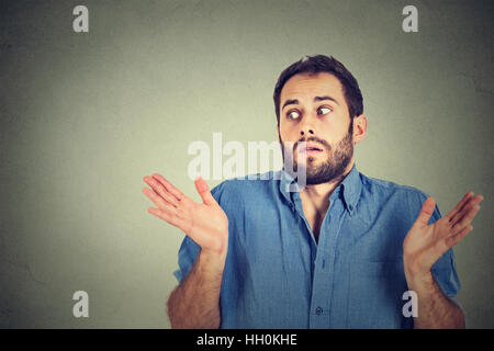Closeup portrait young man shrugging shoulders who cares so what I don't know gesture isolated on gray background. - Stock Photo
