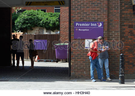 Tourists with a map outside a Premier Inn Hotel in London - Stock Photo
