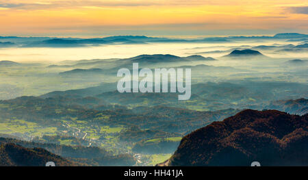 Sunset in the mountains. View of the valley. Golden hour yellow dusk or dawn with sun sunset or sunrise. - Stock Photo