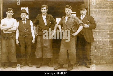 Three blacksmiths and two other men outside a foundry or forge, North America. - Stock Photo