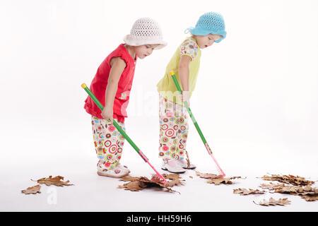 two funny twins raking autumn leaves - Stock Photo