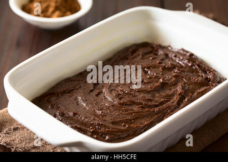 Basic homemade brownie or chocolate cake dough in greased and floured baking pan, photographed on dark wood with - Stock Photo
