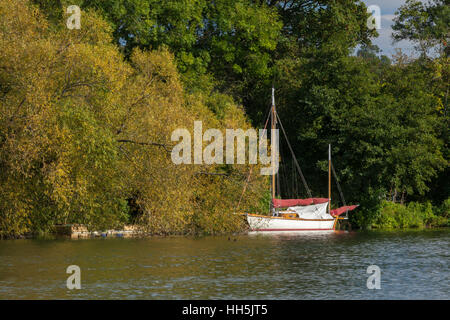 A sailboat moored on the River Thames near Hambleden Lock, in early autumn, Chilterns, Buckinghamshire, England - Stock Photo