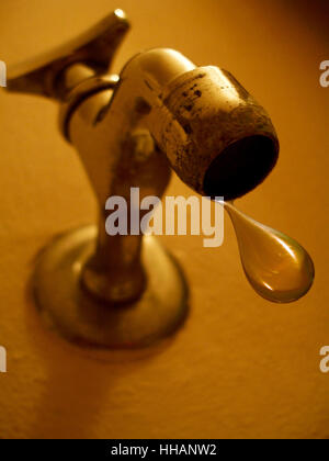 close up view of a large drip of water about to fall from an old faucet mounted on a wall. - Stock Photo
