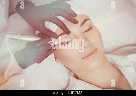 Professional cosmetologist wearing black gloves making permanent makeup - Stock Photo
