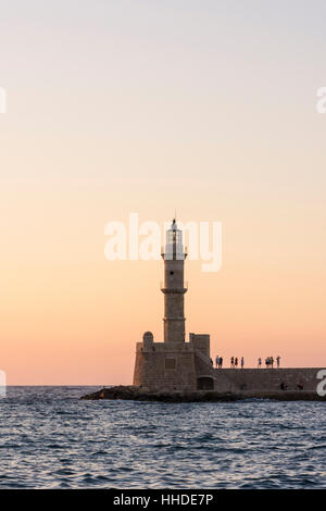 Sunset over the Chania lighthouse at the entrance to the Venetian harbour of Chania, Crete, Greece - Stock Photo