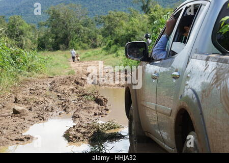 Pickup / Car Stuck in the Mud in Remote Cambodia (Samlout, Battambang) with 2 People in the Distance - Stock Photo