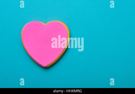 a stack of heart-shaped sticky notes of different colors topped by a pink one with a blank space in it on a blue - Stock Photo