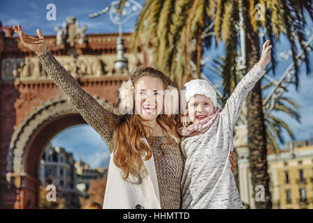 in Barcelona for a perfect winter. Portrait of happy modern mother and child in Barcelona, Spain rejoicing - Stock Photo