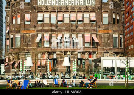 People lounging in front of Hotel New York (formerly Holland-Amerika Lijn building), Rotterdam, Netherlands - Stock Photo