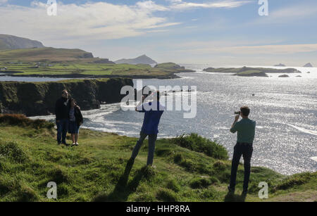 Tourists taking photographs in Ireland on the cliffs at Foilhommerum Bay County Kerry. Their photos being taken - Stock Photo