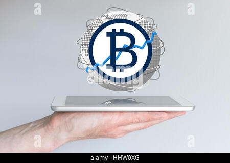 Increasing of global bitcoin currency exchange rate concept with hand holding tablet - Stock Photo