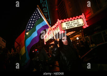 San Francisco, USA. 20th Jan, 2017. A protestor carries an LGBTQ flag through the Castro District during a protest - Stock Photo
