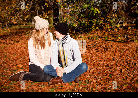 young couple in autumn park with colorful leaves outdoors - Stock Photo
