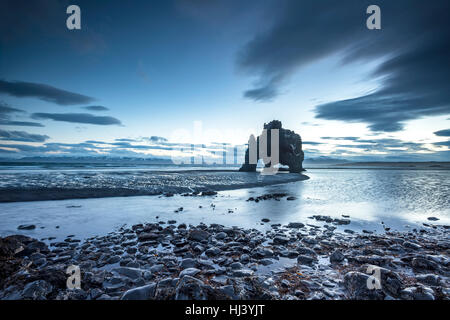 A landmark beach in Iceland called Dinosaur Rock protrudes 50 feet out of the shallow water during an early morning - Stock Photo