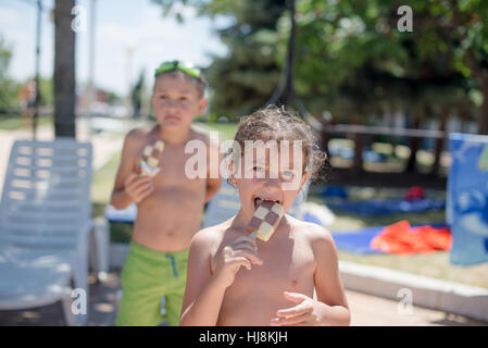 Girl and boy eating ice-crams on the beach - Stock Photo